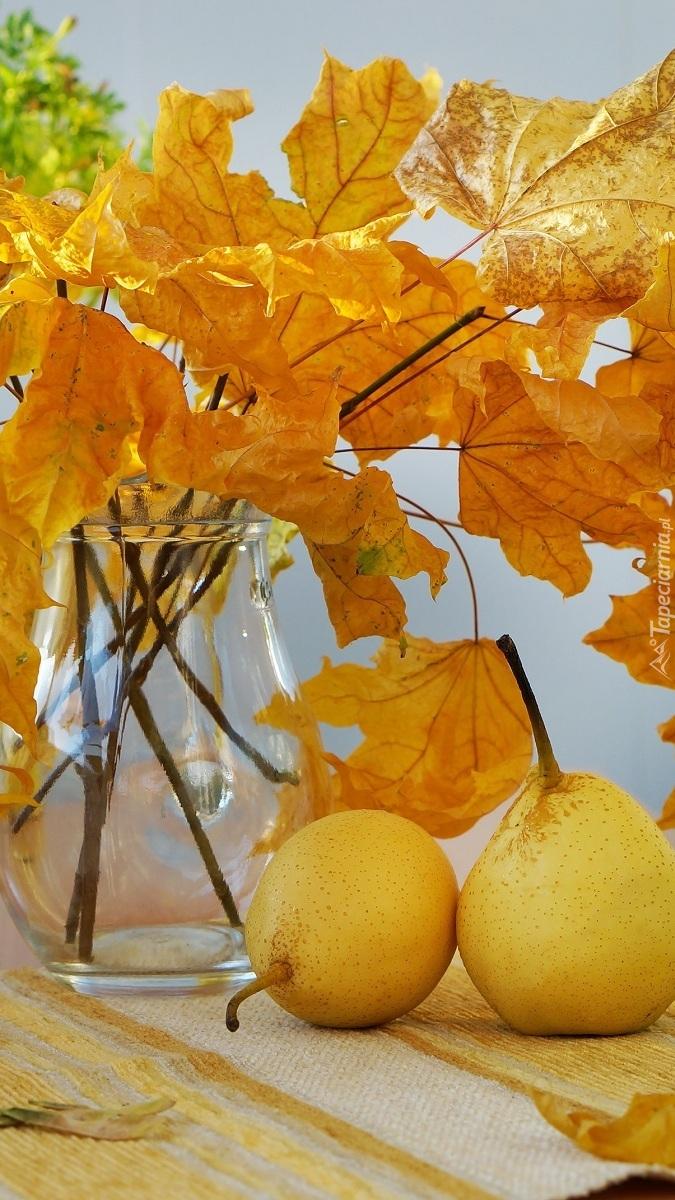 Liście klonu w wazonie obok gruszek