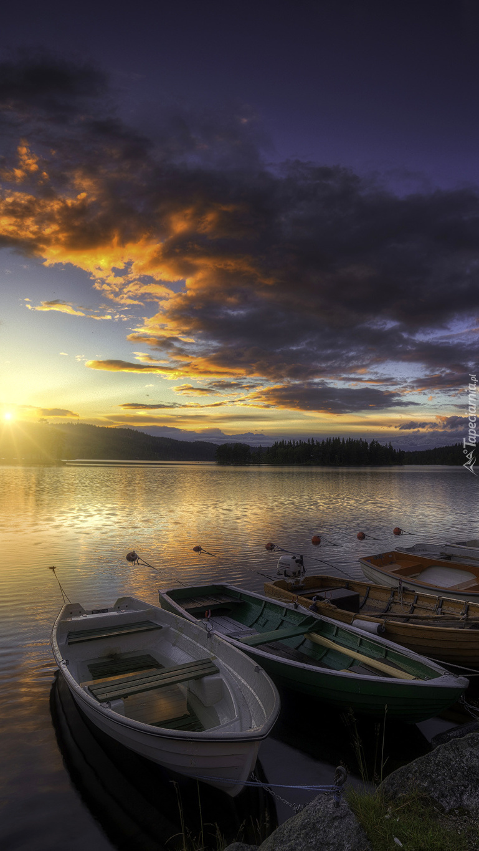 Łódki na brzegu jeziora o zachodzie słońca