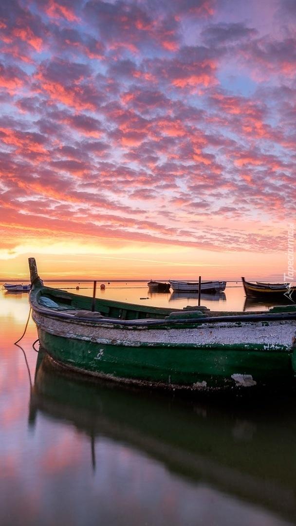 Łódki na jeziorze pod kolorowym niebem