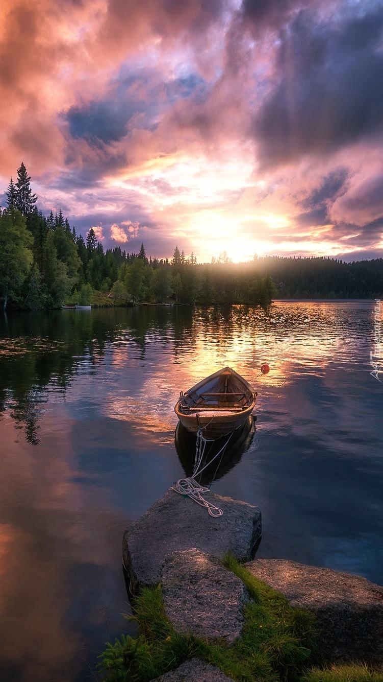 Łódź na jeziorze przycumowana do kamienia