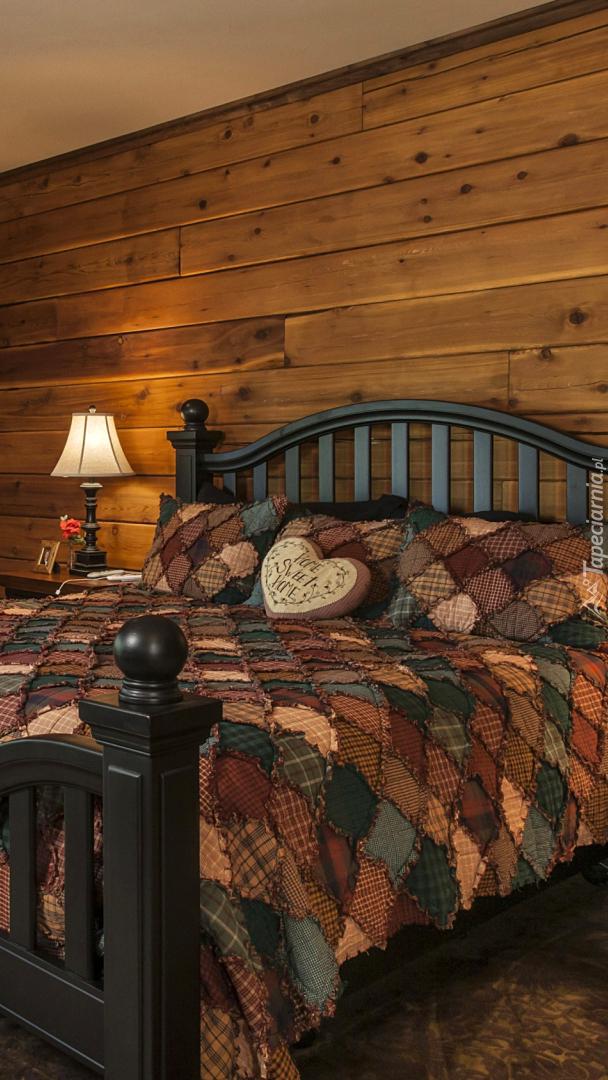Łóżko w sypialni z drewnianymi ścianami