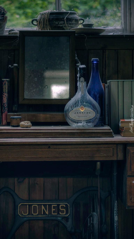 Lustro i butelki na starej maszynie do szycia