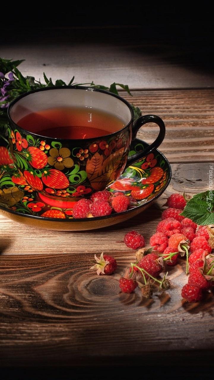 Maliny obok kolorowej filiżanki z herbatą