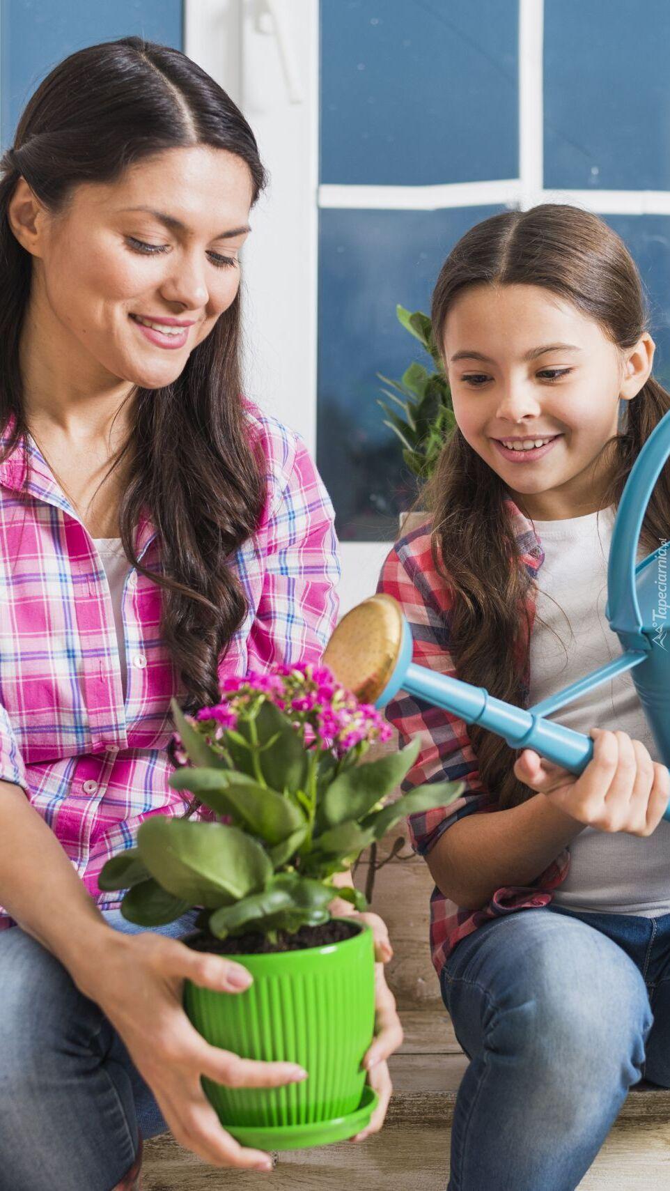 Mama z córką podlewające kwiaty