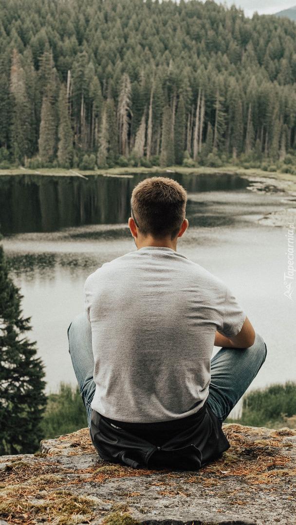 Mężczyzna na skale nad jeziorem