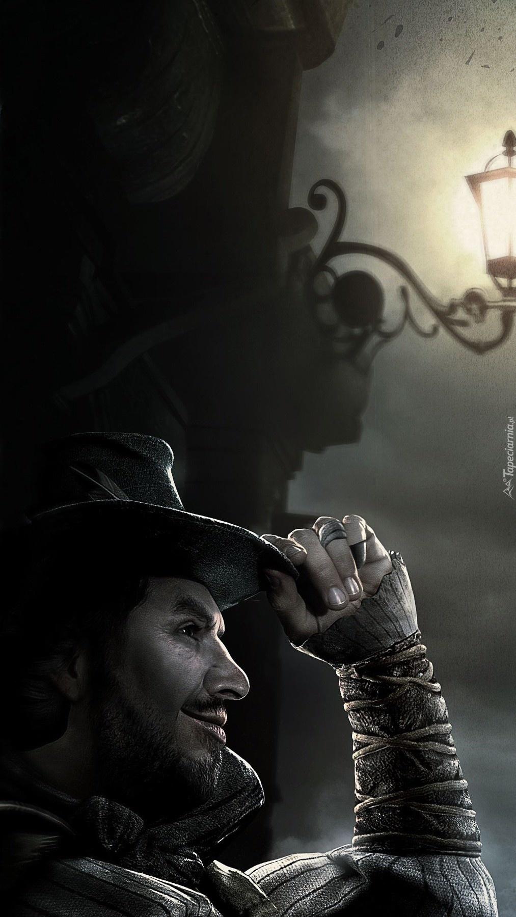 Mężczyzna w kapeluszu obok latarni