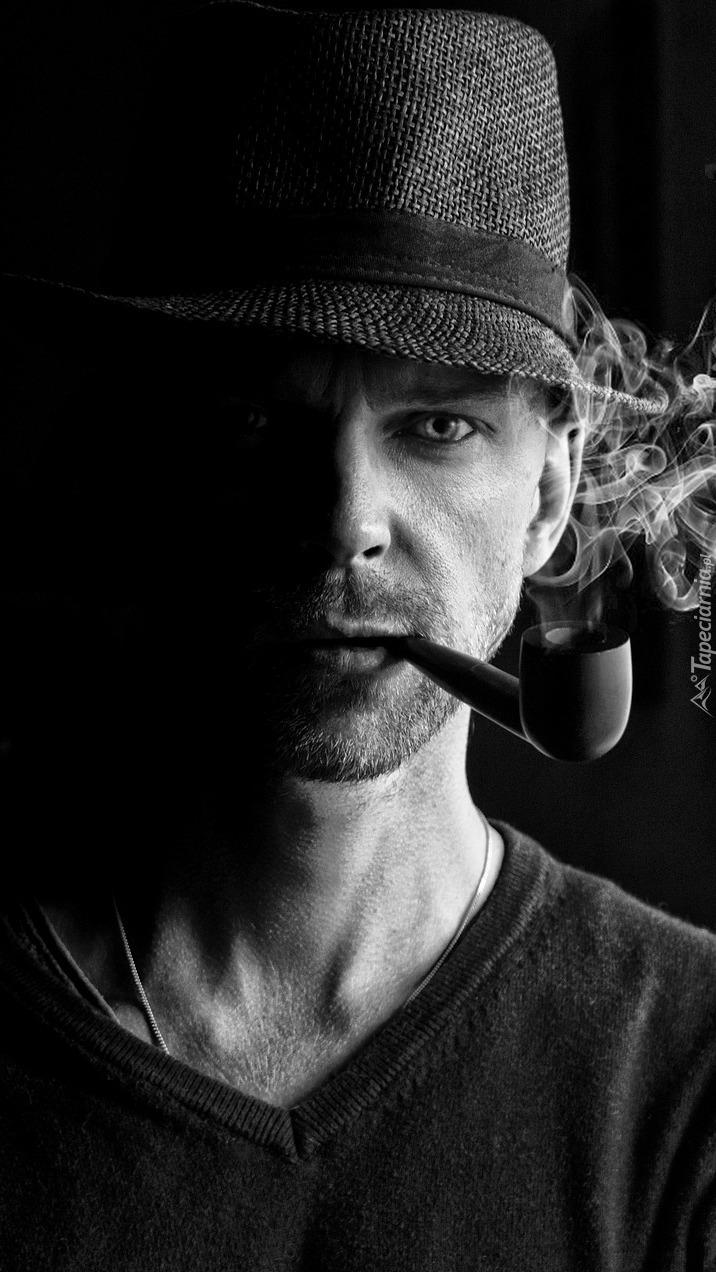 Mężczyzna w kapeluszu z fajką