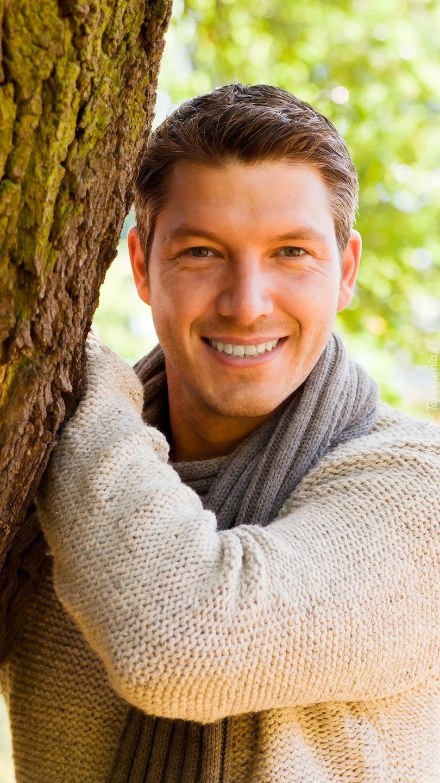 Mężczyzna w szaliku pod drzewem