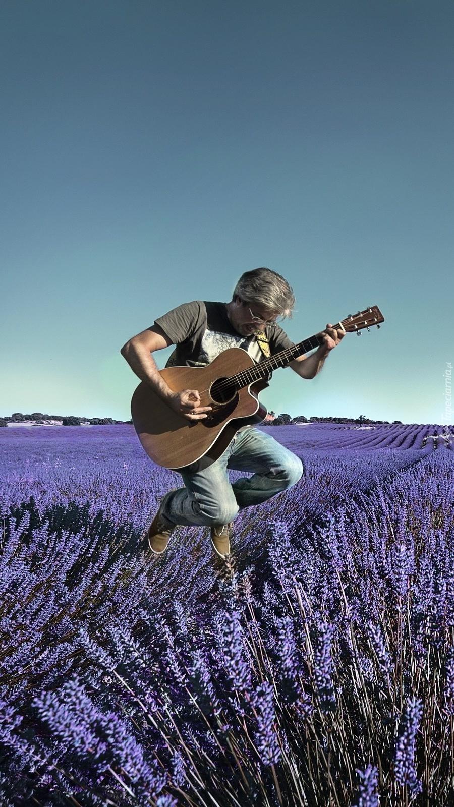Mężczyzna z gitarą na polu lawendowym
