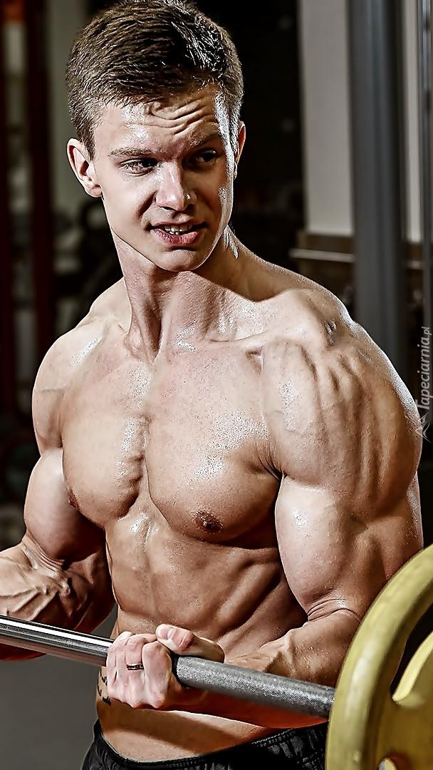Mężczyzna z sztangą na siłowni