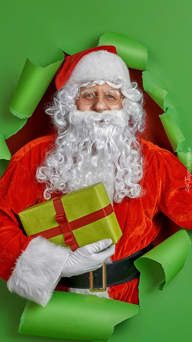 Mikołaj z prezentem na zielonym tle
