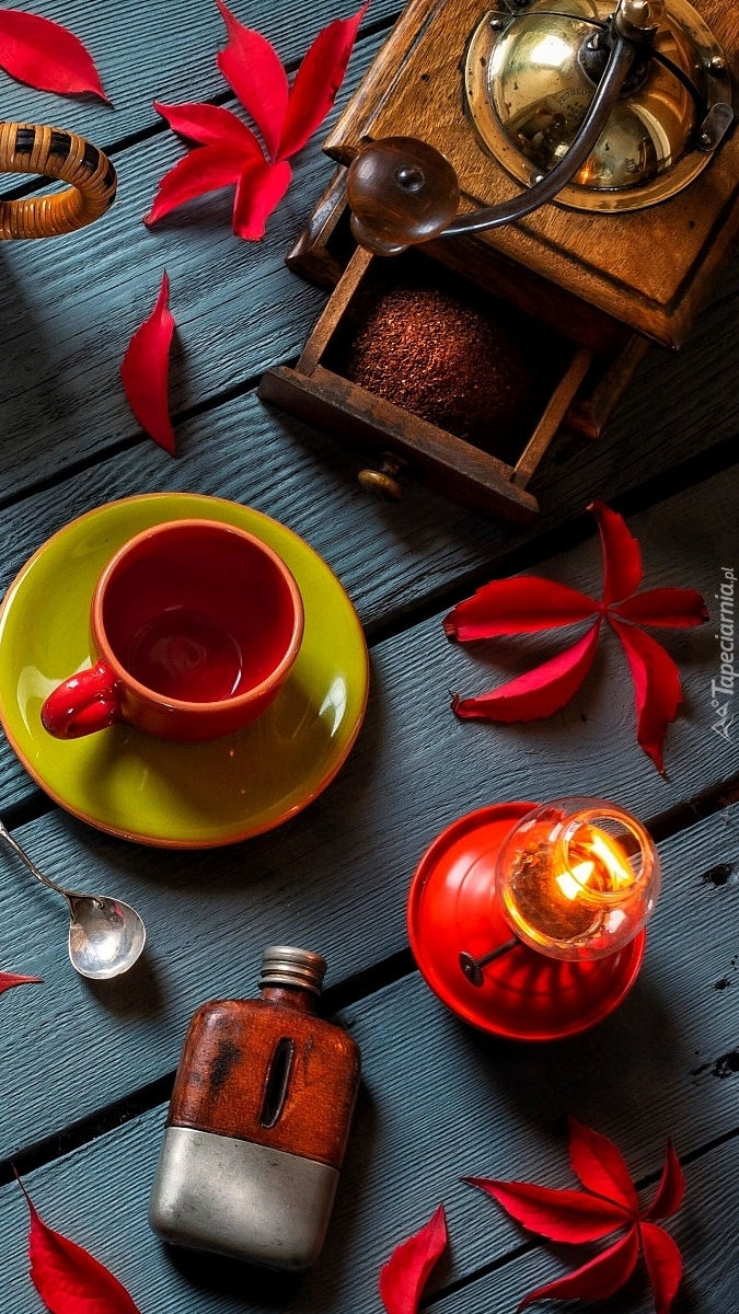 Młynek do kawy obok liści i filiżanki