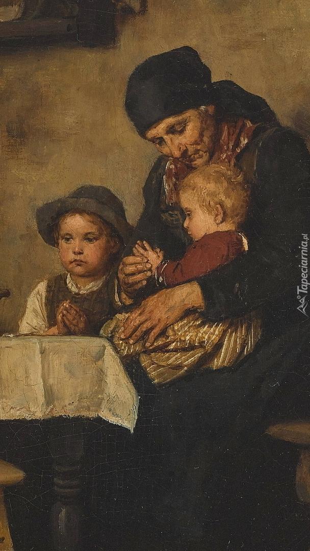 Modląca się przy stole kobieta z dziećmi