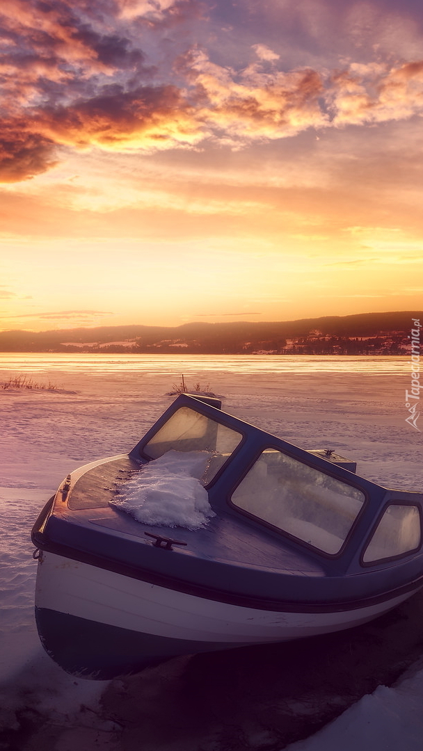Motorówka na brzegu jeziora zimą
