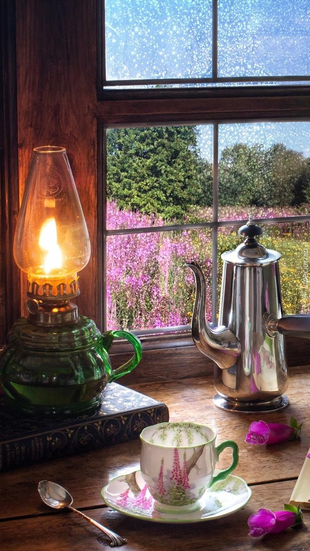Naftowa lampa i dzbanek przy oknie