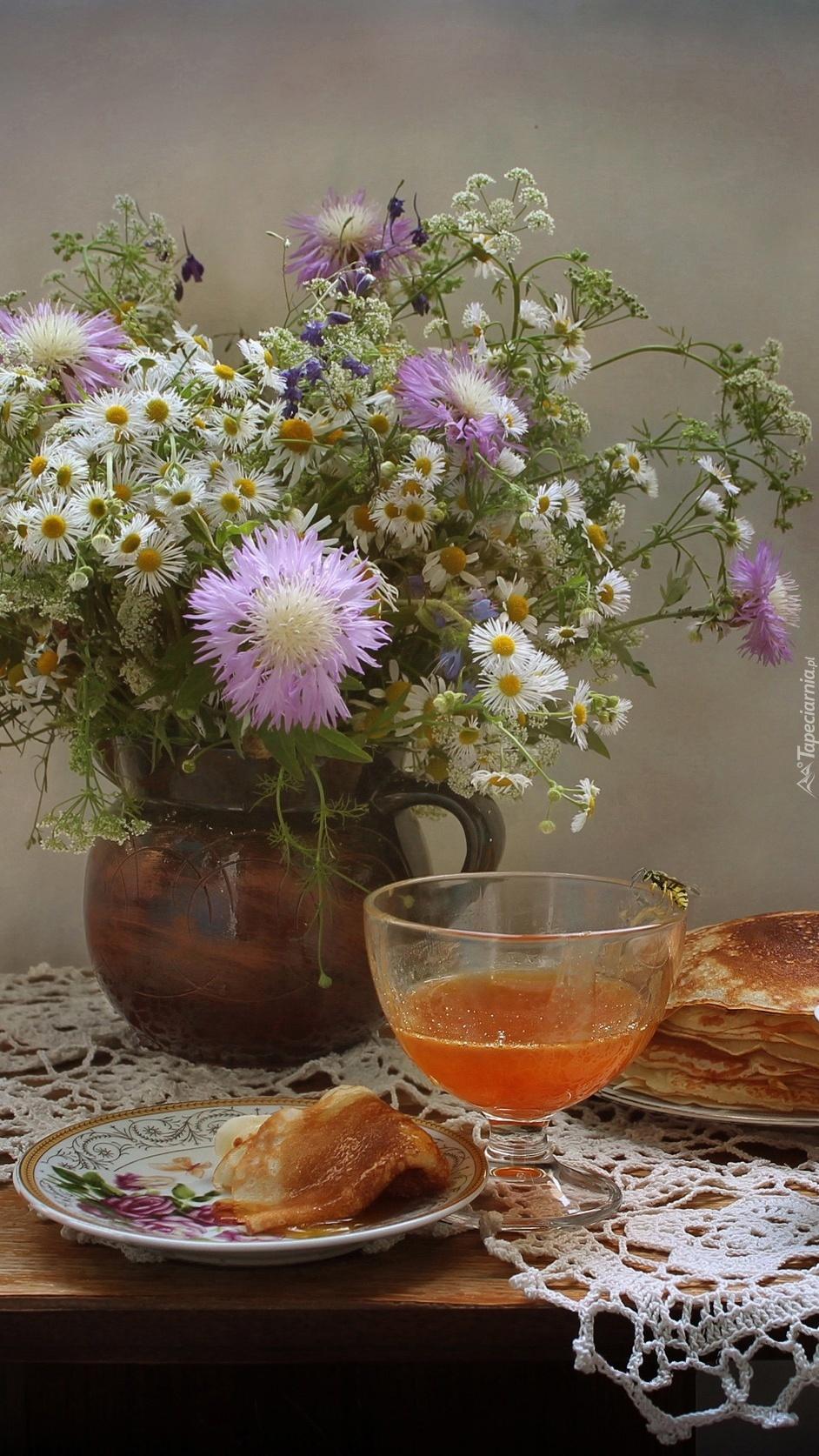 Naleśniki na talerzach obok dzbanka z kwiatami