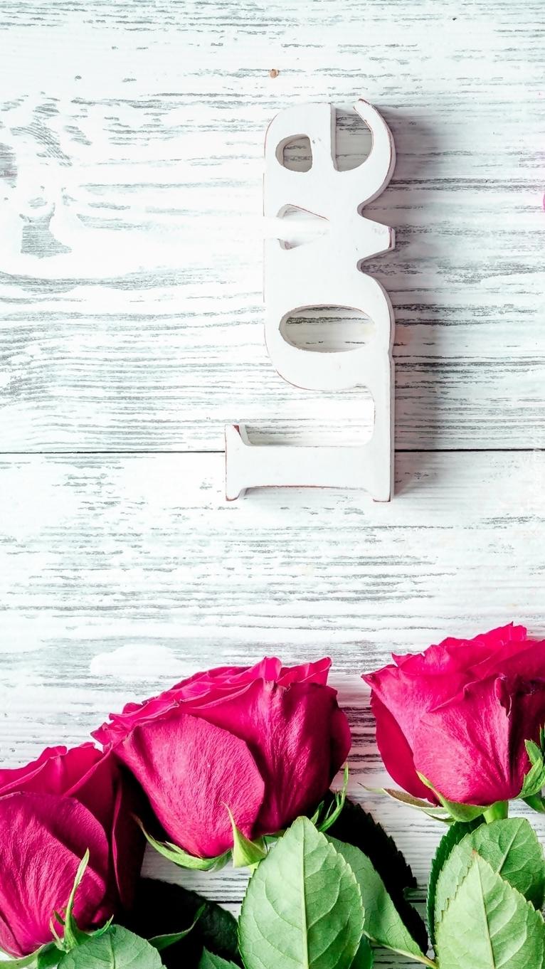Napis Love z czerwonymi różami