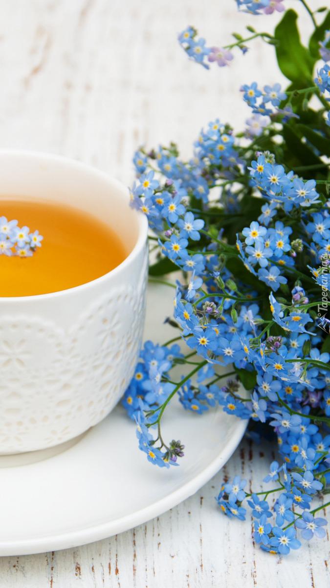Niezapominajki obok filiżanki z herbatą