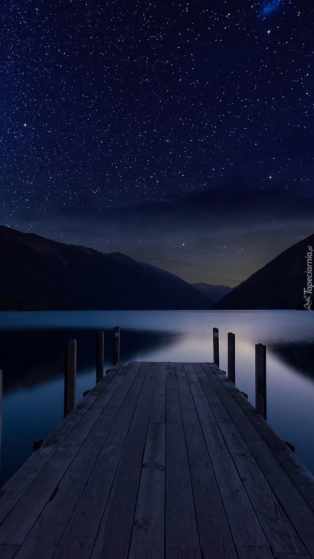 Noc z gwiazdami nad jeziorem i pomostem
