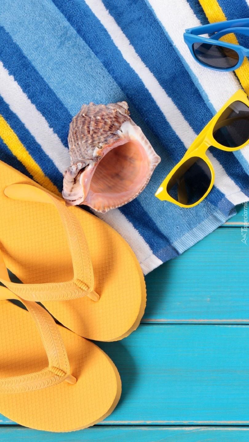 Okulary, klapki i muszla pozostawione na ręczniku