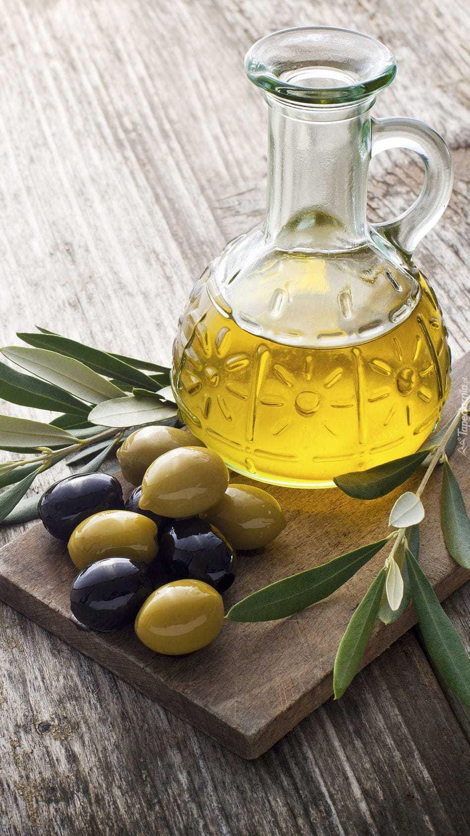 Oliwa z oliwek w dzbanuszku na desce obok oliwek