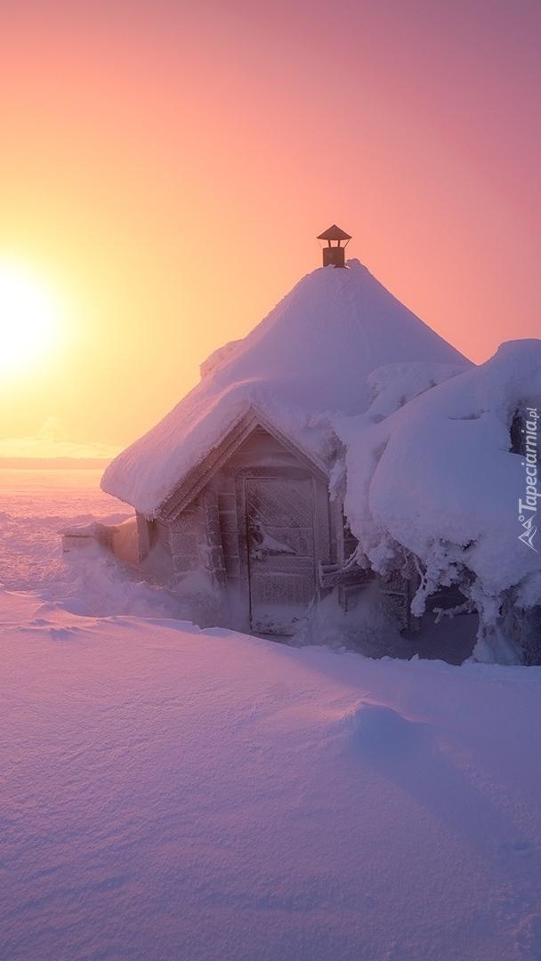 Ośnieżona chata o wschodzie słońca