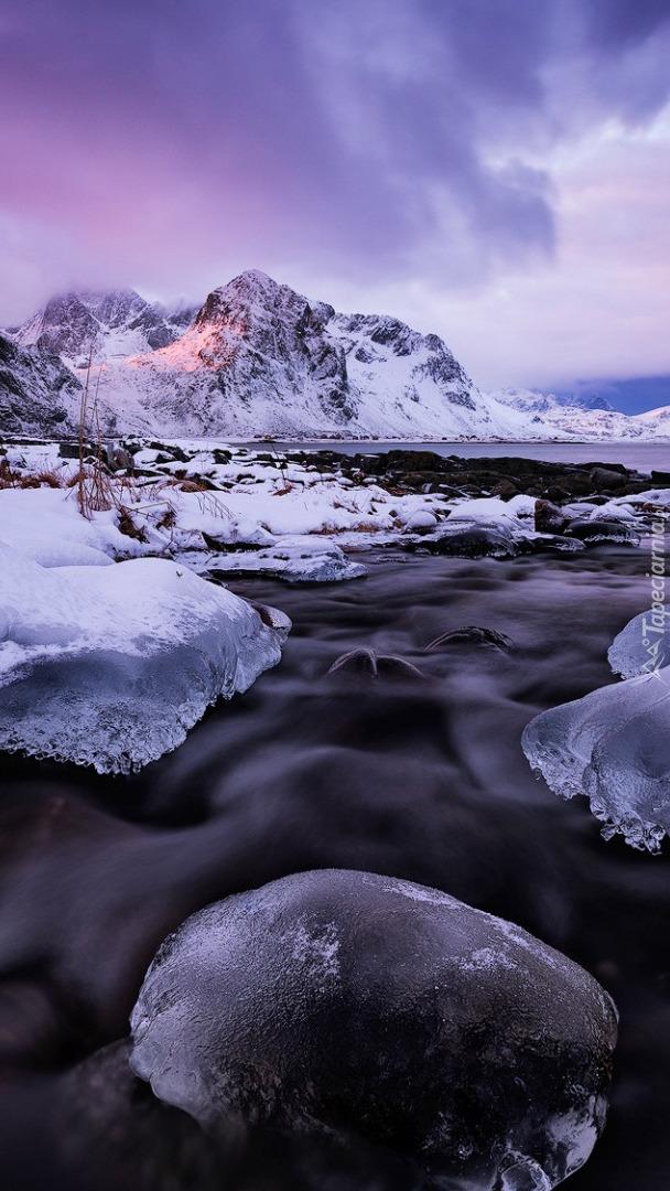 Ośnieżone góry i oblodzone kamienie w morzu