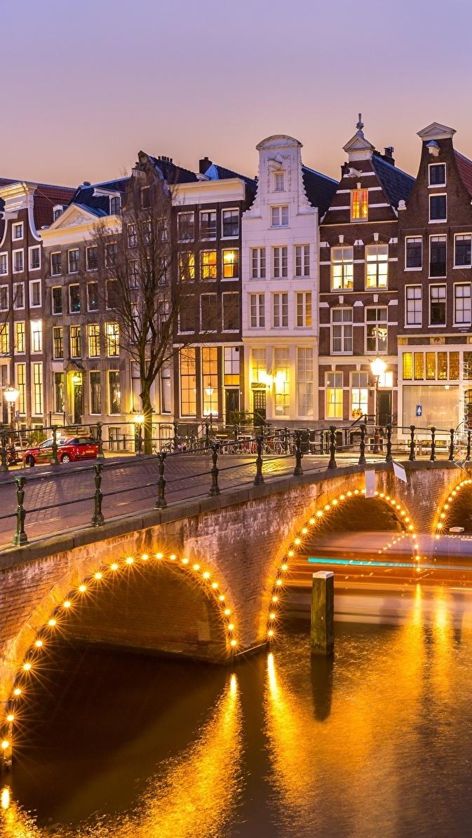 Oświetlone domy i most nad kanałem w Amsterdamie