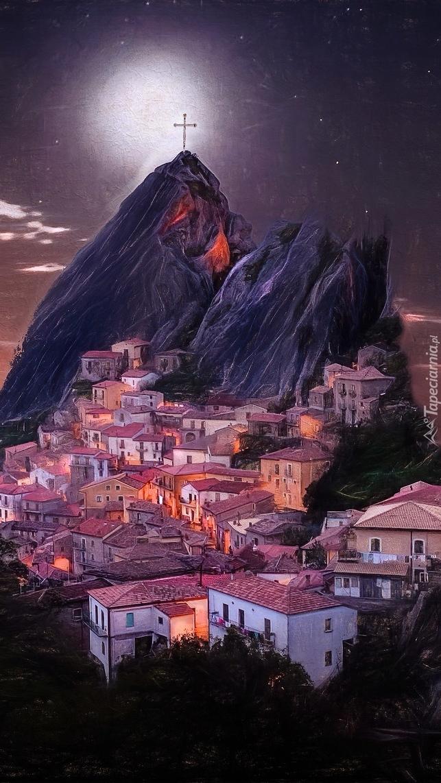 Oświetlone domy na tle góry