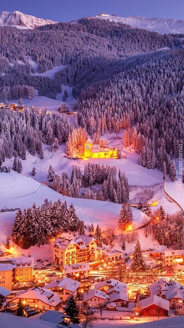 Oświetlone domy w zimowej górskiej dolinie