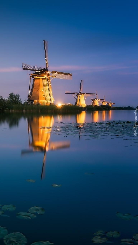 Oświetlone wiatraki nad rzeką