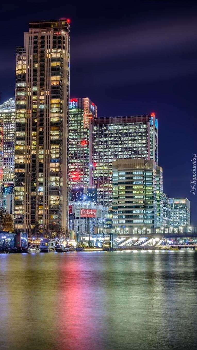 Oświetlone wieżowce nad dokiem w Londynie