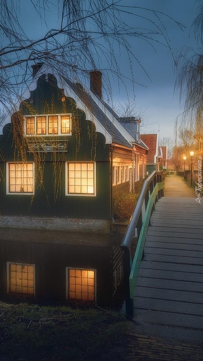 Oświetlony dom i most nad kanałem