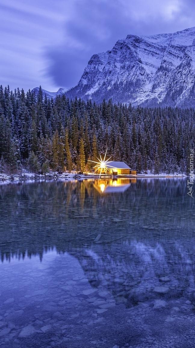 Oświetlony dom pod lasem nad jeziorem Lake Louise