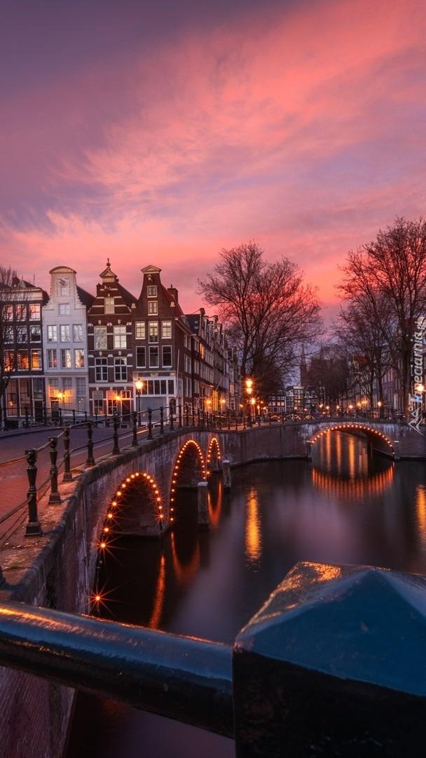 Oświetlony most nad kanałem w Amsterdamie