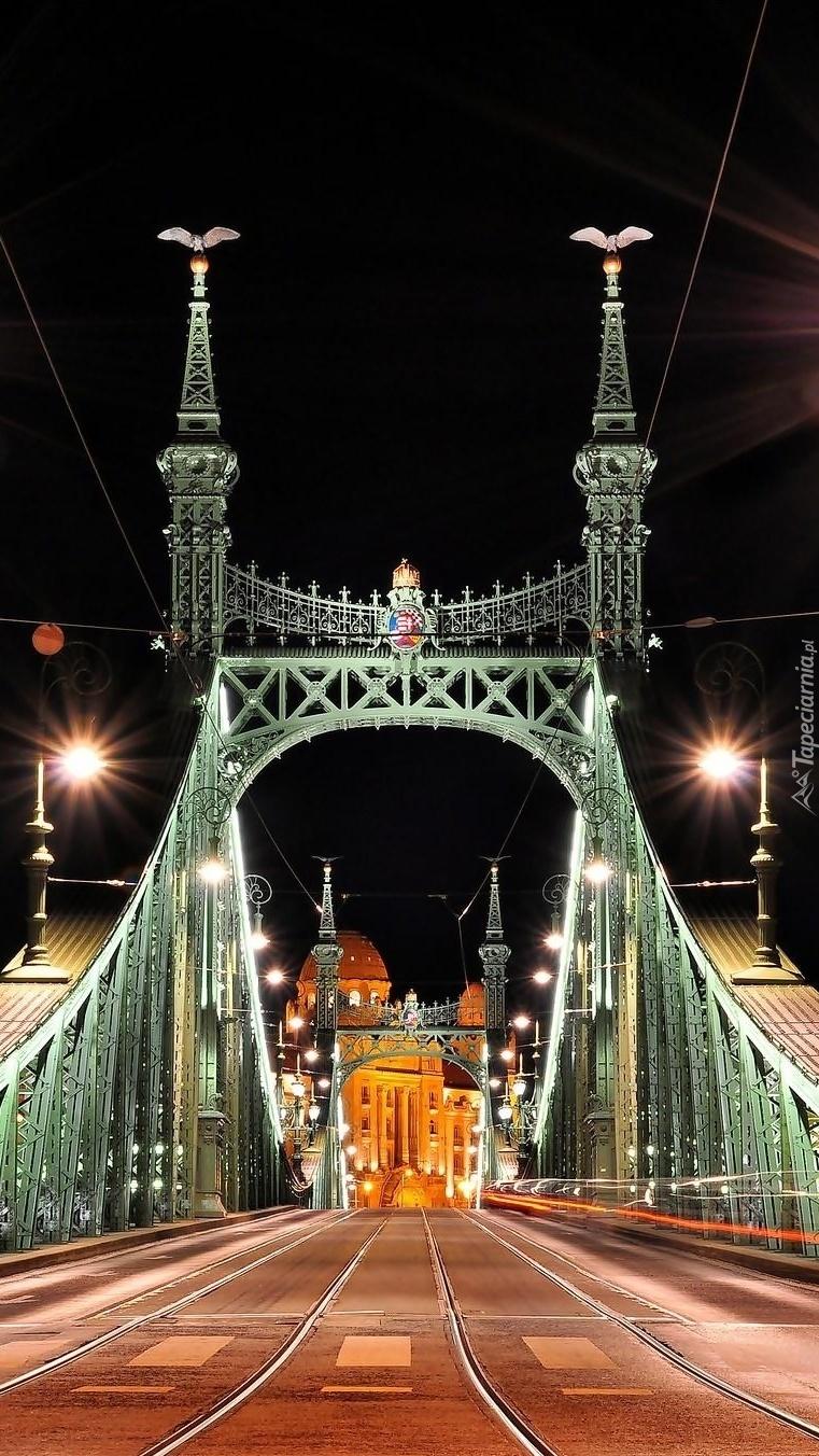 Oświetlony żelazny most zaprasza do miasta