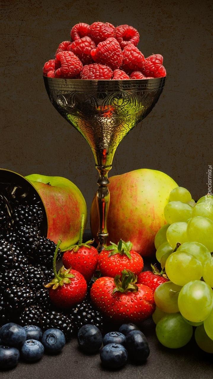 Owoce obok pucharka z malinami