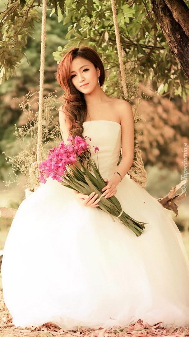 Panna młoda z bukietem kwiatów na huśtawce