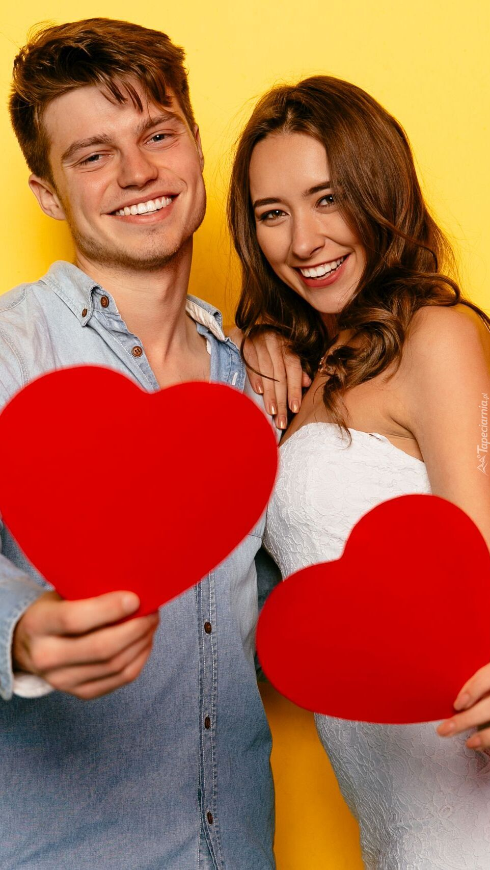 Para z czerwonymi sercami w dłoniach