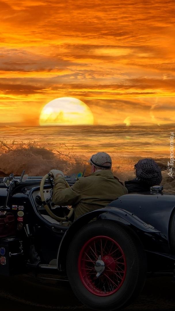 Pasażerowie w samochodzie oglądający zachód słońca nad morzem