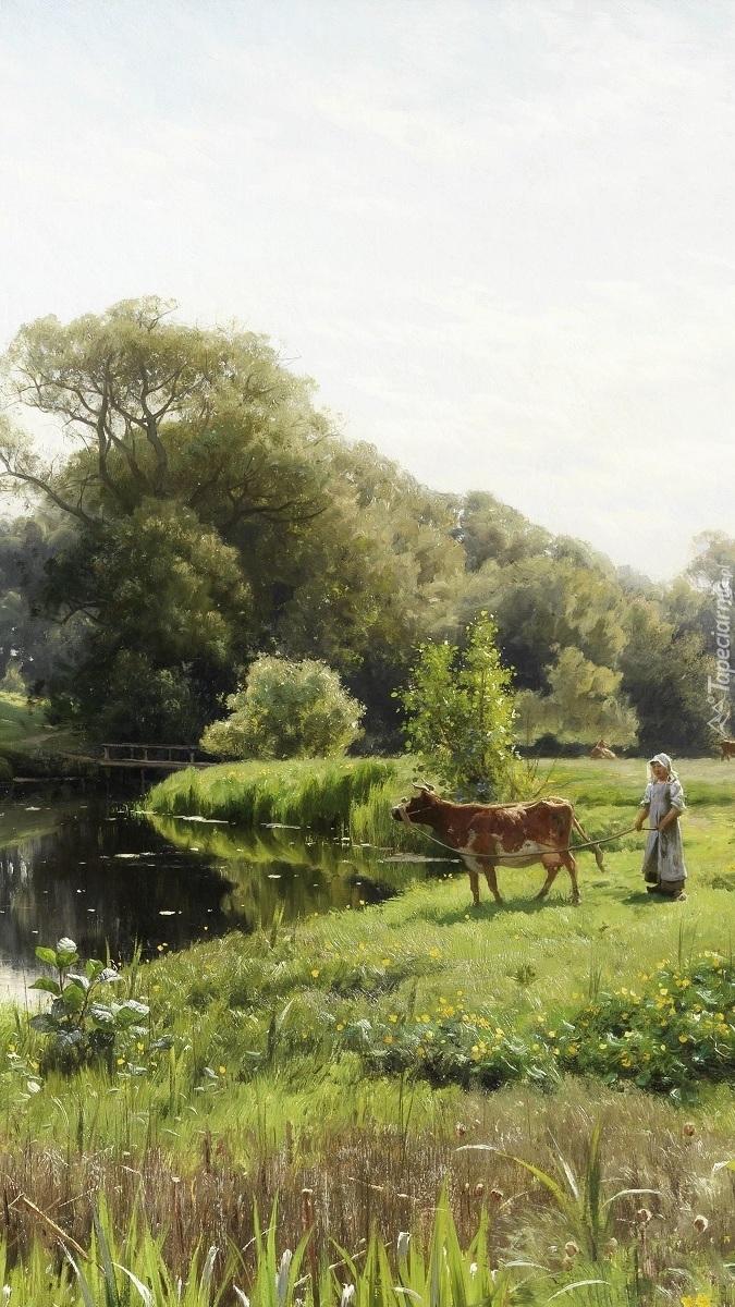 Pasterka z krówką na łące przy rzece