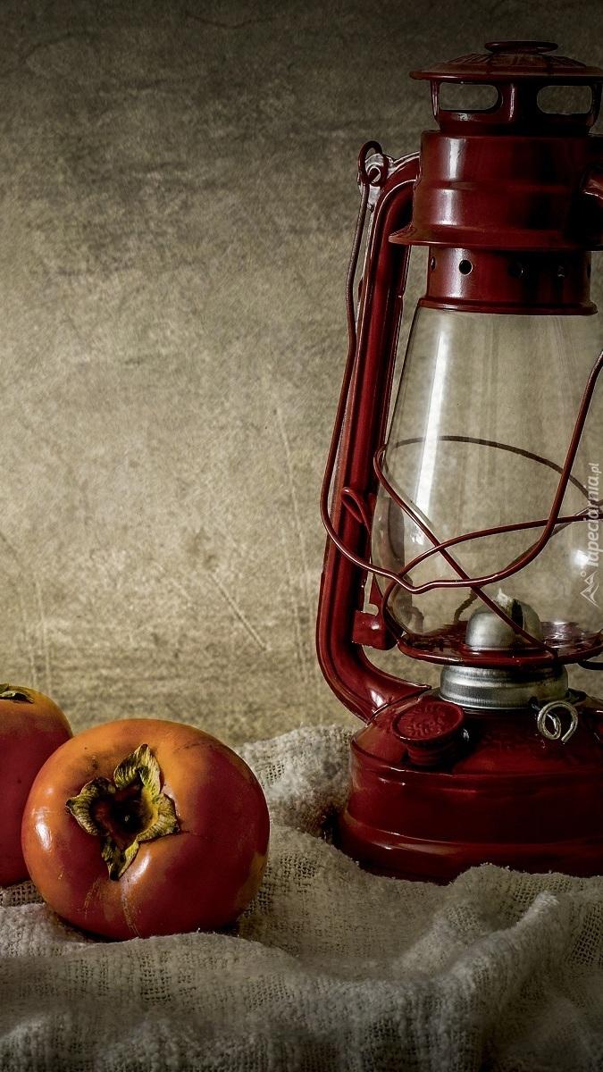 Persymony obok lampy naftowej