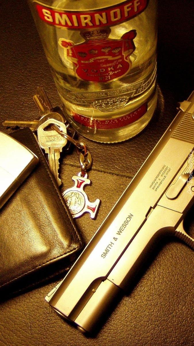 Pistolet obok butelki Smirnoffa