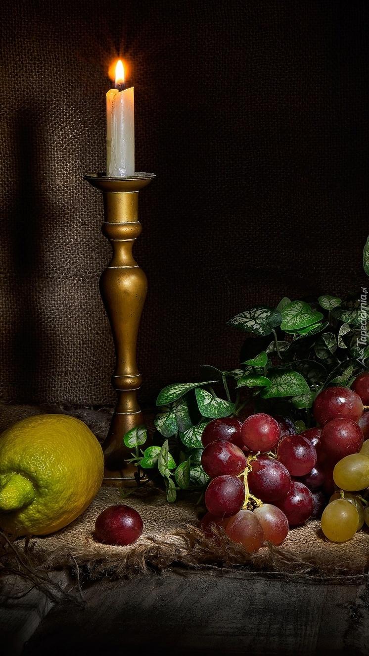Płonąca świeca obok winogron