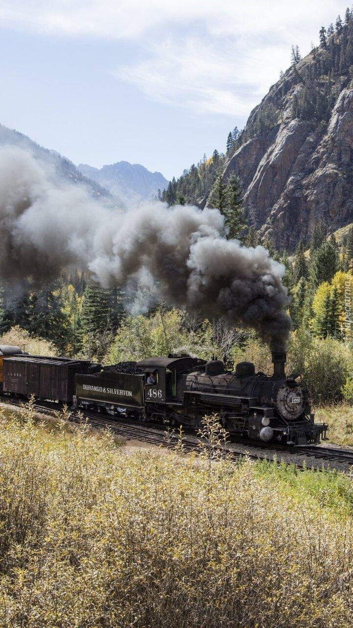 Pociąg z dymiąca lokomotywą w górach