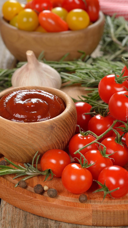 Pomidory na gałązce obok miseczki z keczupem