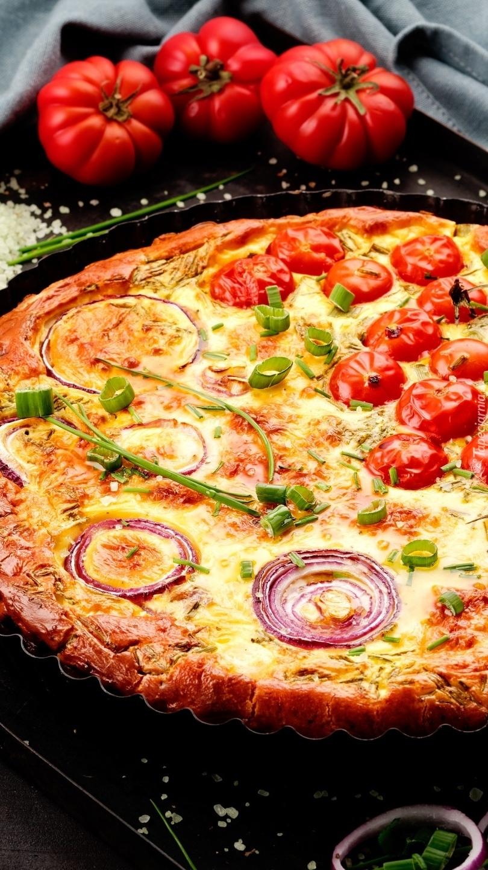 Pomidory obok pizzy w foremce