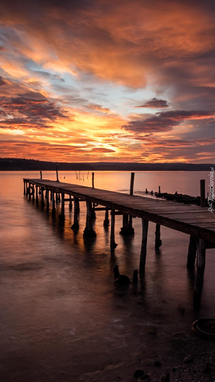 Pomost nad jeziorem przy zachodzie słońca