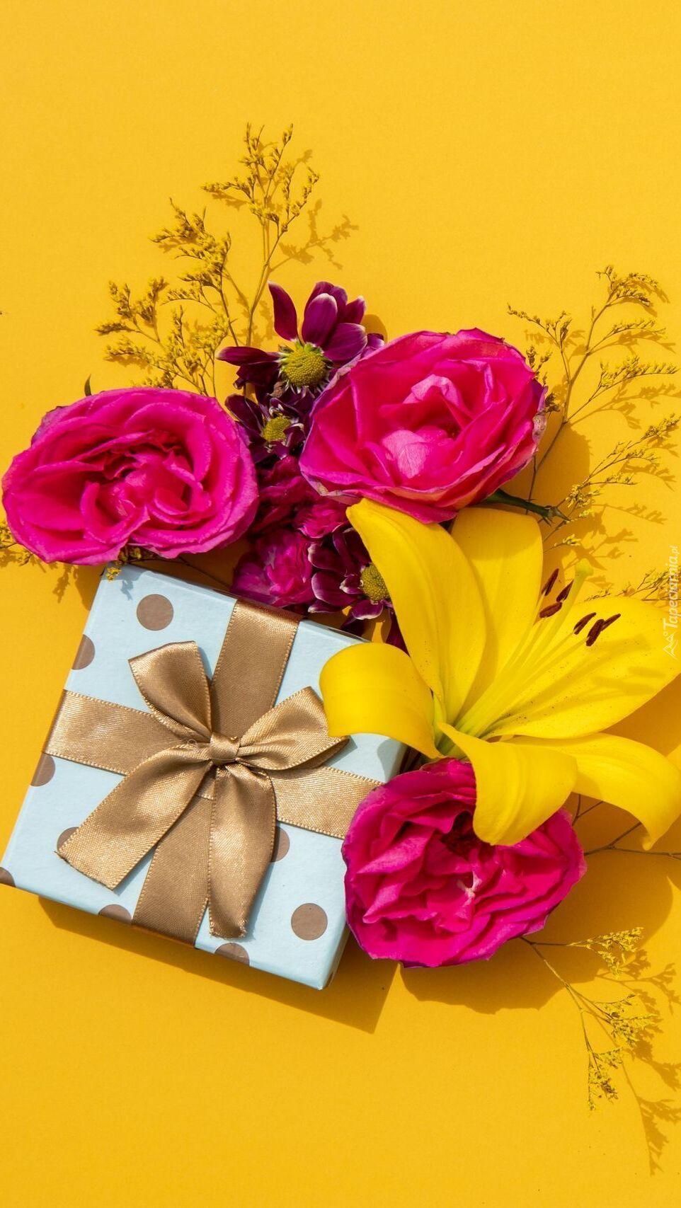 Prezent obok lilii i róż