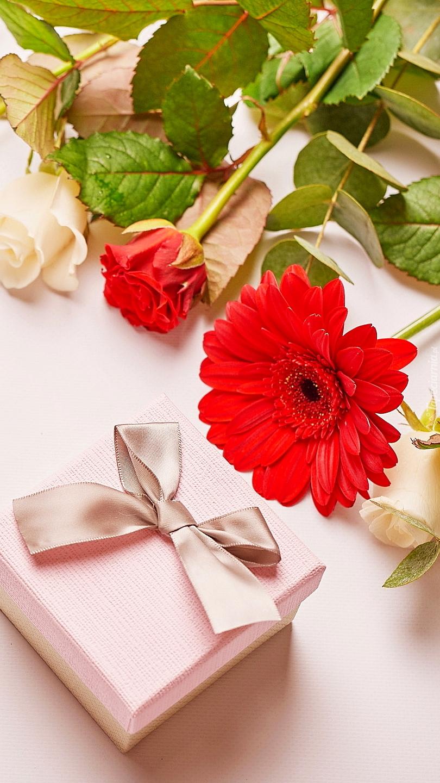 Prezent obok róż i gerbery